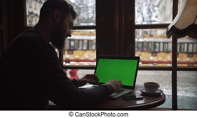 Man using Laptop with Green Screen in Cafe