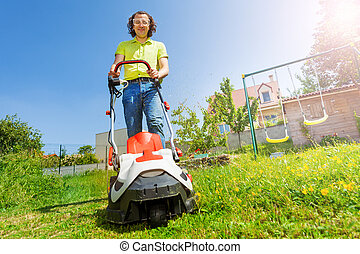 Man using lawnmower grass clipper at the backyard