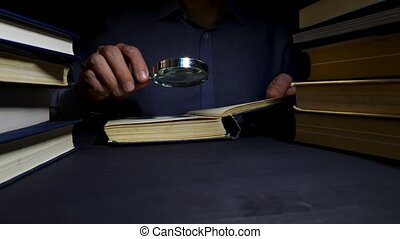 Man using magnifying glass for reading the book. ...
