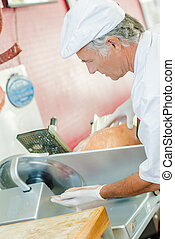 Man using meat slicing machine