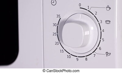 Man using microwave. Closing door of the microwave oven and setting cooking time