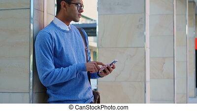Man using mobile phone against pillar in the city 4k