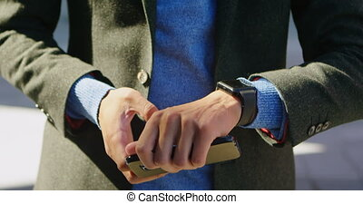 Man using mobile phone and smartwatch on street 4k - Mid...