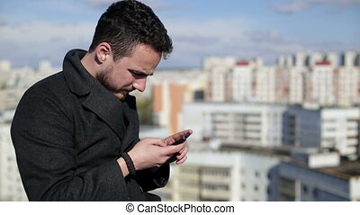 Man using mobile phone and writing sms on a house roof...