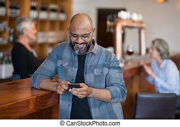 Man using mobile phone at counter in bar