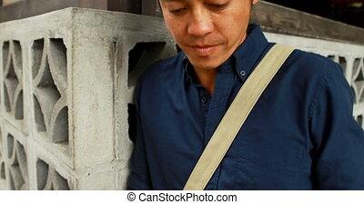 Man using mobile phone at outdoor cafe 4k - Smiling man...