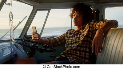 Man using mobile phone in camper van 4k - Side view of ...