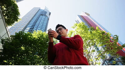 Man using mobile phone on street 4k - Low angle view of man...