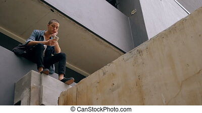 Man using mobile phone while sitting in corridor 4k - Young ...
