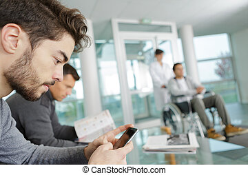 man using mobile phone while waiting a at clinic