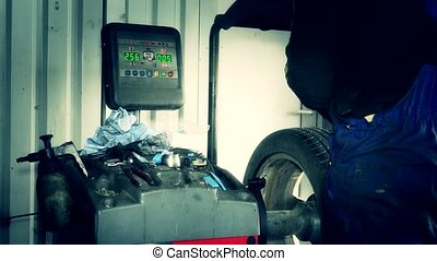 Man using modern computerized equipment for car tire...