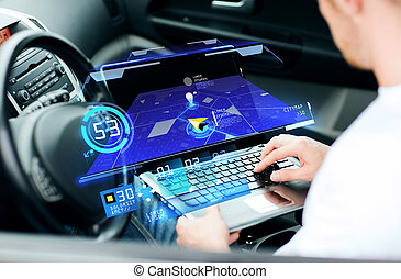 man using navigation on laptop computer in car