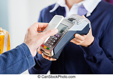 Man Using NFC Technology To Pay Bill At Cinema - Cropped...