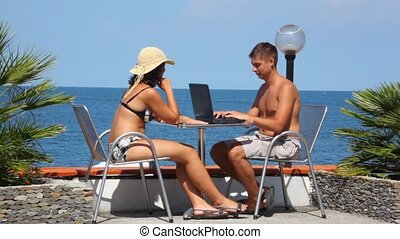 man using notebook and woman with cell phone sits at table, sea in background