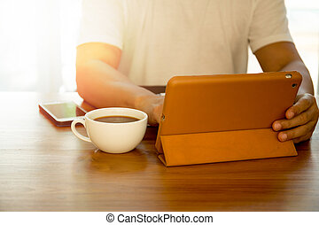 Man using notepad with coffee and cell phone on the table