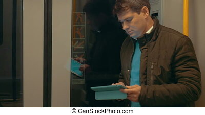 Man using pad in high speed subway train
