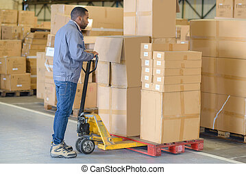 Man using pallet truck to move cardboard boxes