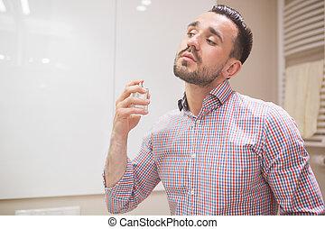 Man using perfume before date