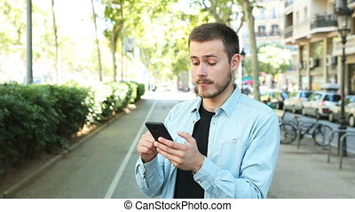 Man using smart phone and saying yes looking at camera in the street