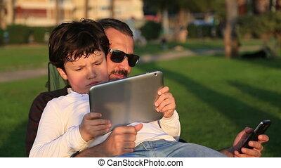 Man using phone son using tablet