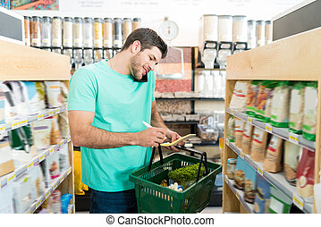 Man Using Phone While Buying Food Products In Store