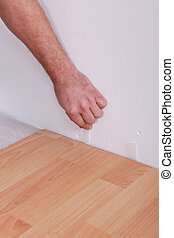 Man using plastic wedges whilst laying parquet