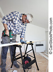 Man using power drill on plank of wood