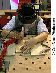 Man using power tool to carve wood