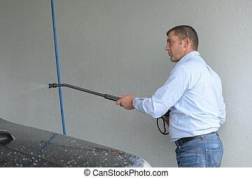 Man using power washer