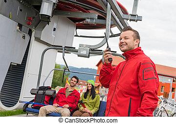 Man using radio starting chair lift - Man in red coat using...