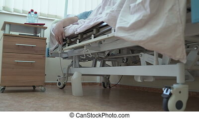 Man using remote control to adjust hospital bed in a patient room