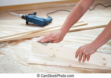 Man using sandpaper - Close-up of a man using sandpaper,...