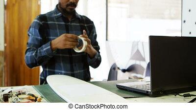 Man using sellotape for making skateboard 4k - Man using...