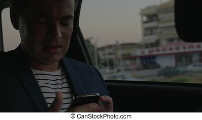 Man using smart phone in the car