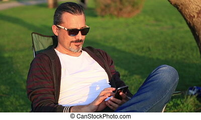 Man using smart phone in the park