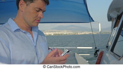 Man using smart phone on the yacht