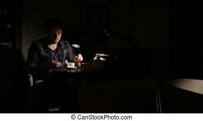 Man using smartphone and drinking tee in cafe