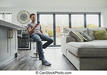 Man Using Smartphone At Home - Man is relaxing in the living...