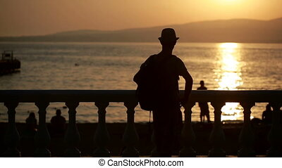 man using smartphone by the sea. tourist walks along the promenade. photograph