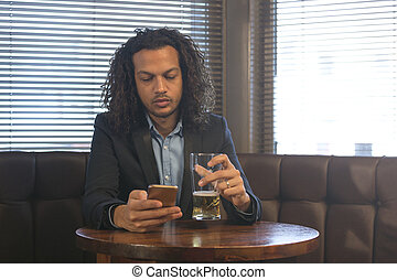 Man using smartphone in a bar