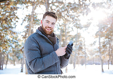 Man using smartphone in winter park