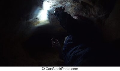 Man using smartphone laying on ground into very narrow cave with hand flashlight