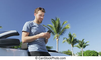 Man using smartphone leaning on convertible car. Low angle view of young successful male professional texting using mobile cell smart phone against clear blue sky. Man driver getting in car driving.