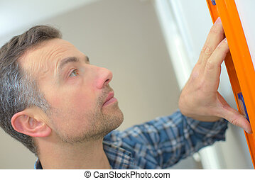 man using spirit level on white wall at home