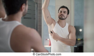 Man Using Spray Deodorant On Underarm For Bad Smell - Young...