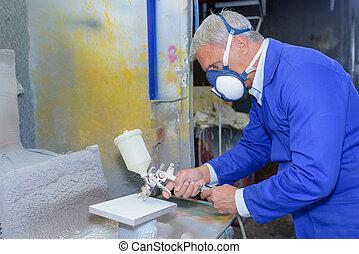 Man using spray paint gun