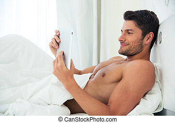 Man using tablet computer at home