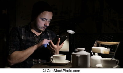 Man using tablet computer in cafe in the evening