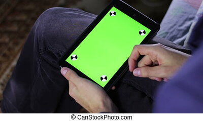 Man Using Tablet Computer on the Couch  with Green Screen