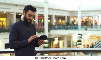 Man using tablet in shopping mall. Lot of people at the background